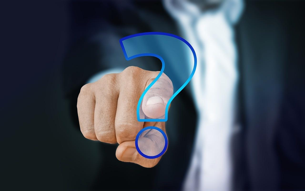 Finger eines Mannes im Anzug mit Fragezeichen.